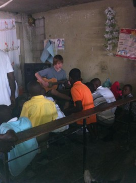 The Brothers Dube - Liam showing how to play the guitar in Haiti.