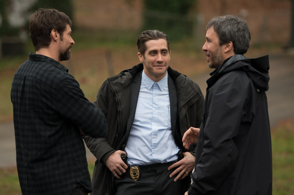 "Stars Hugh Jackman, and Jake Gyllenhaal with director Denis Villeneuve (R) on the set of ""Prisoners"""