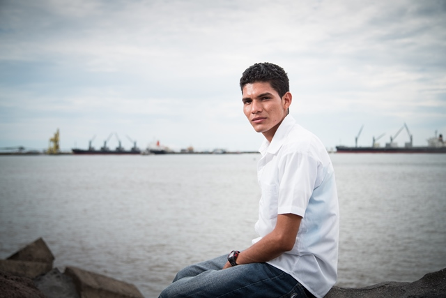 José Miguel, age 20, with the port where he used to work in the distance. Image: Paul Bettings, 2013