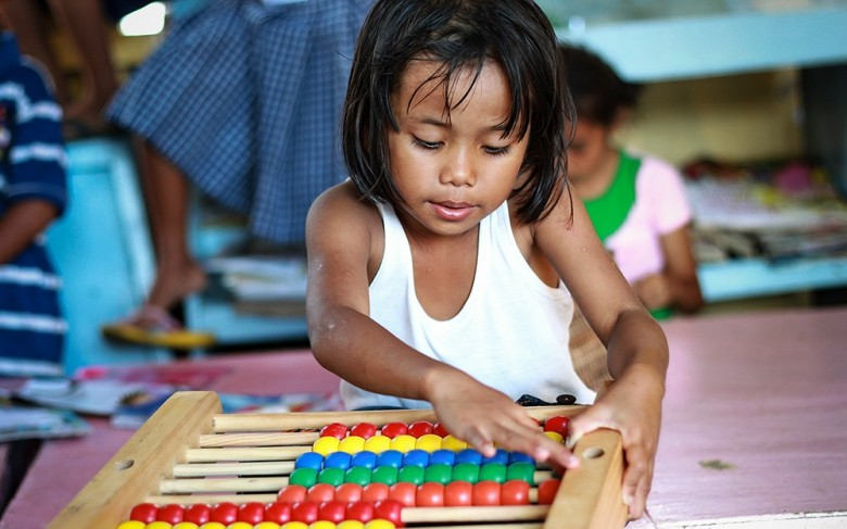 ©2013 ORLANDO DUCAY JR./WORLD VISION A girl plays with a colorful wooden toy at World Vision's Child-Friendly Space in Tabogon, northern Cebu, Philippines.
